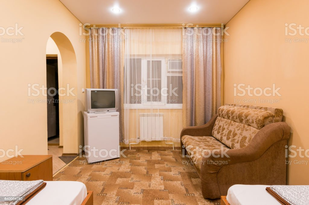 The interior of a small room with sofa bed and two single beds, window, TV and fridge stock photo