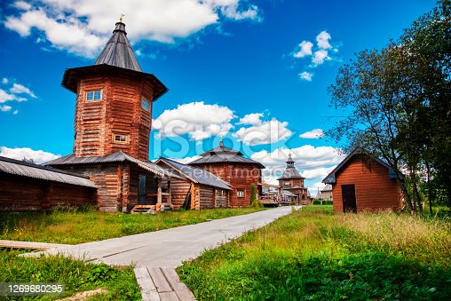The interior of a wooden fortress made of logs with a tower on the background of a summer landscape and a blue sky with white clouds. Traditional old architecture