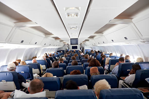 The interior of an airplane with passengers stock photo