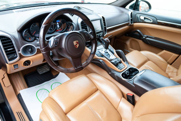 The interior of the car Porsche Cayenne Diesel 958 2012 year with a view of the steering wheel, dashboard, seats and multimedia system with light brown leather trim Novosibirsk, Russia - 08.01.2018: The interior of the car Porsche Cayenne Diesel 958 2012 year with a view of the steering wheel, dashboard, seats and multimedia system with light brown leather trim porsche stock pictures, royalty-free photos & images