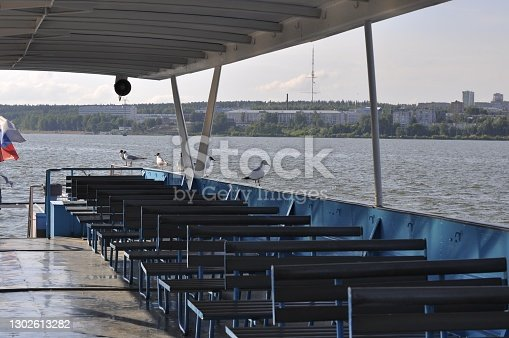 A small simple ship, interior, for excursions on the lake, walking tourists on the water. The interior of the yacht, on the lake, against the background of the city standing on the shore of the reservoir. Izhevsk, Russia.