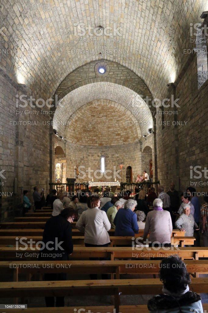 El funcionamiento interno y el altair de la piedra románico Santo Mary Church (Iglesia de Santa Maria) durante la celebración de una Misa en Ainsa, un pequeño pueblo rural en las montañas del Pirineo Aragonés Español - foto de stock