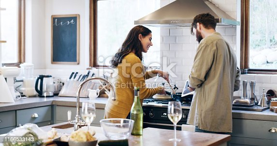 Shot of a young couple using a digital tablet while preparing a meal at home