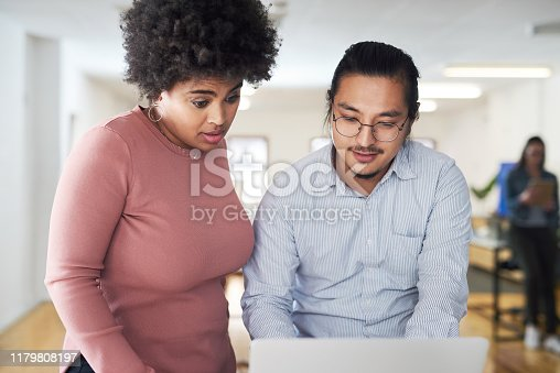 Shot of a young businessman and businesswoman using a laptop in a modern office