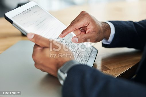 Cropped shot of an unrecognizable businessman using a digital tablet
