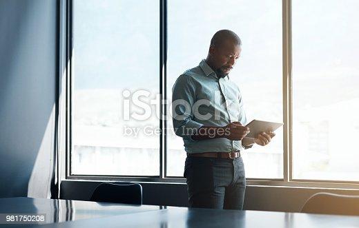 Shot of a mature businessman using a digital tablet in a modern office