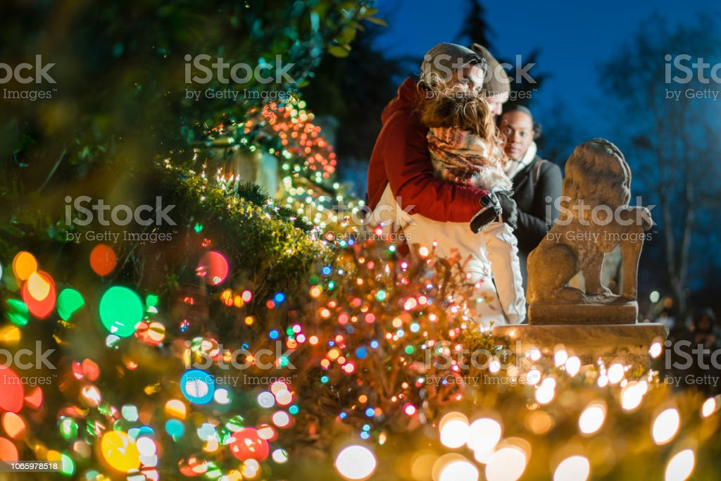 The interracial loving couple, teenagers, the beautiful Caucasian white 17-years-old long haired girl and handsome Latino Hispanic 18-years-old boy, hugs surrounded by Christmas Lights  and having fun in the cold winter day in Brooklyn, New York stock photo