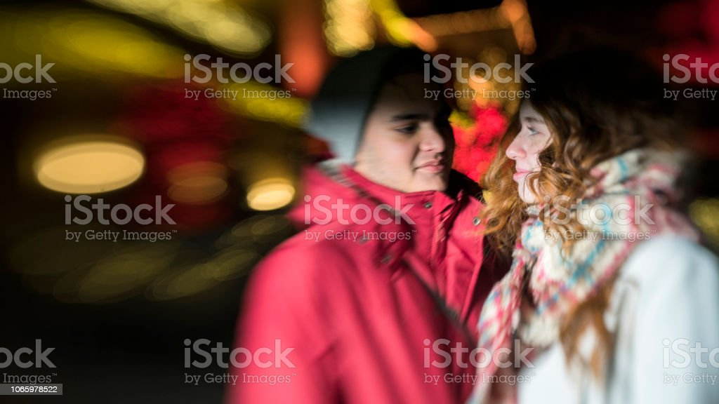 The interracial loving couple, teenagers, the beautiful Caucasian white 17-years-old long haired girl and handsome Latino Hispanic 18-years-old boy, watching Christmas Lights  and having fun in the cold winter day in Brooklyn, New York stock photo
