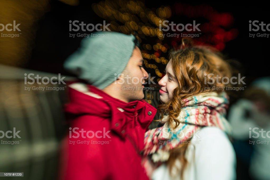 O casal amoroso interracial, adolescentes, o bonito caucasiano branco 17 anos de idade menina de cabelos longos e lindo Latino hispânico rapaz de 18 anos de idade, observando as luzes de Natal e se divertindo no dia frio de inverno em Brooklyn, Nova Iorqu - foto de acervo