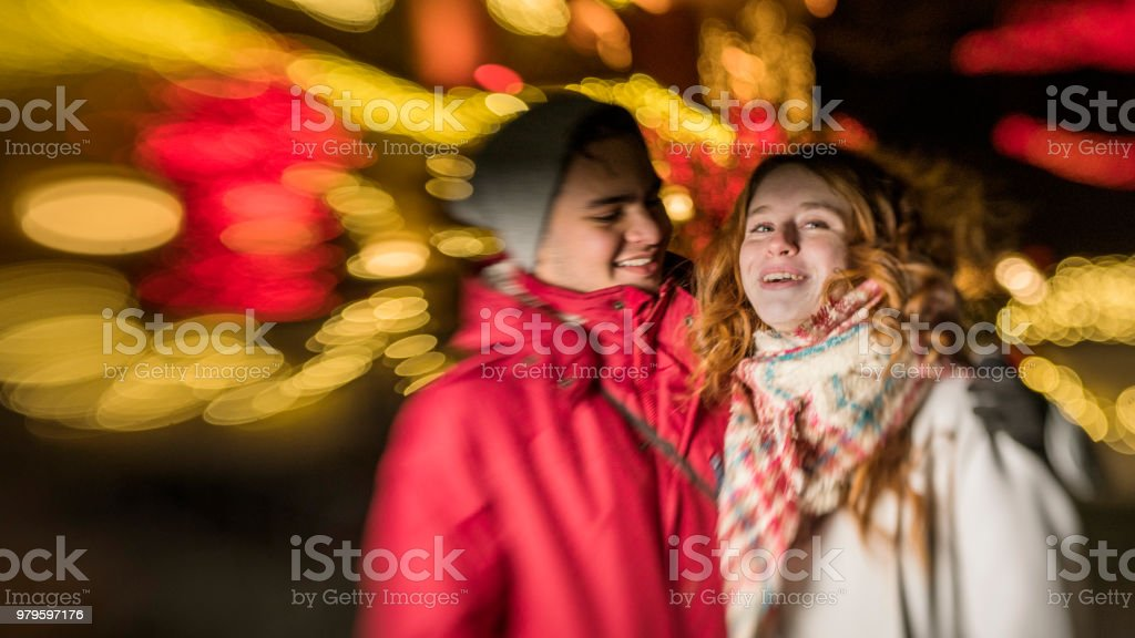 The interracial loving couple, teenagers, the beautiful Caucasian white 17-years-old long haired girl and handsome Latino Hispanic 18-years-old boy, watching Christmas Lights  and having fun in the cold winter day in Brooklyn, New York – zdjęcie