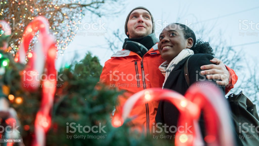 The interracial loving couple, the beautiful Black young woman and handsome young man, hugs, watching Christmas Lights and having fun in the cold winter day in Brooklyn, New York. stock photo