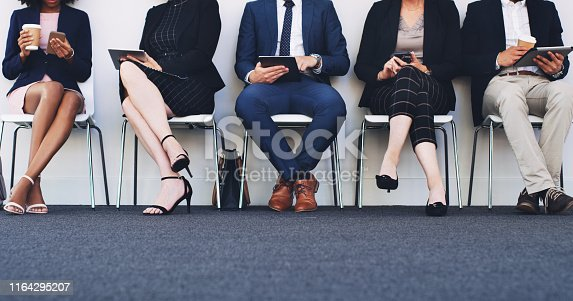 Cropped shot of a diverse group of businesspeople using technology while sitting in a line in the office