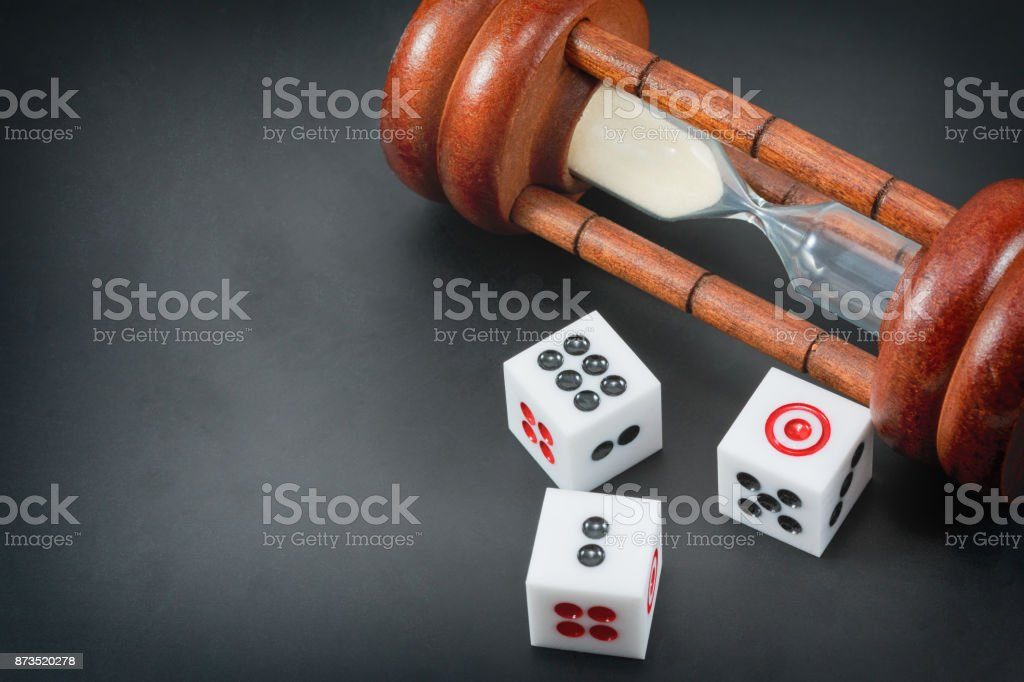 The investment risk with different of time. dice and sandglass on the black desk and free space for text. High Risk High Return or  Low Risk High Return. stock photo