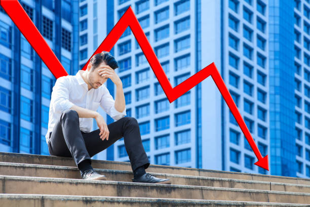The Investor sitting alone on the stair outdoor. Young business man crying abandoned lost in depression of Red arrow fall dawn,economy or Stock market down, stock photo