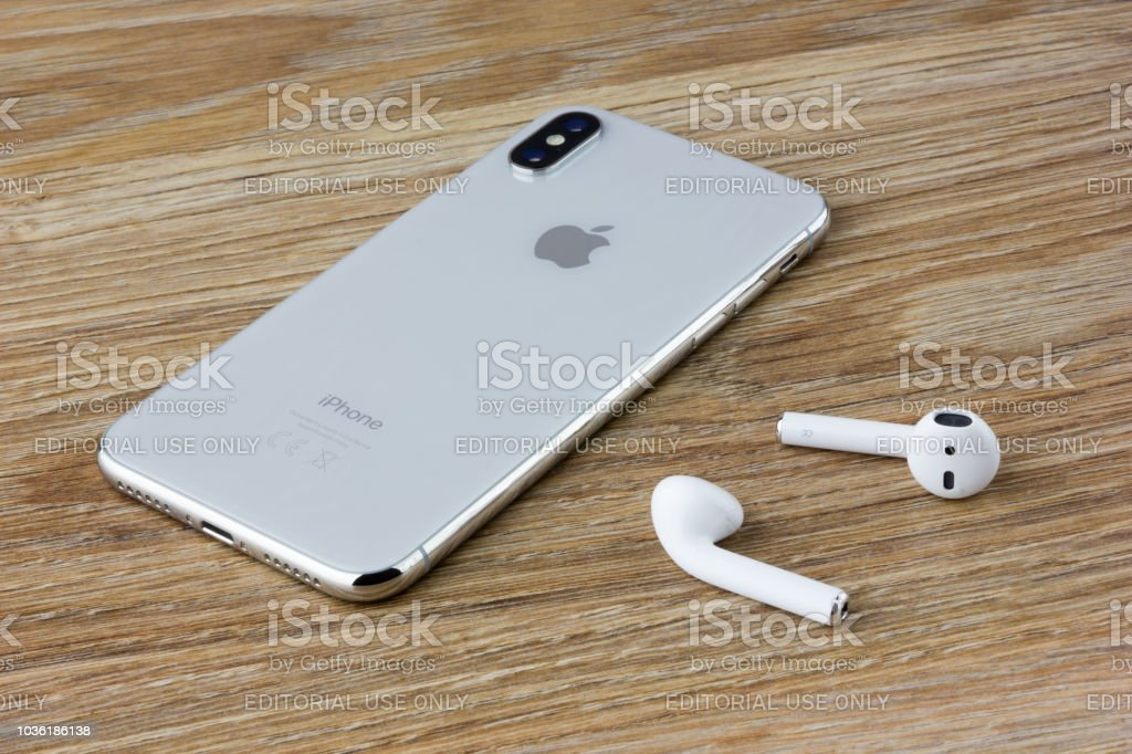 The Iphone 10 Lies On A Wooden Table Next To The Wireless Headphones Airpods From The Apple Stock Photo Download Image Now Istock
