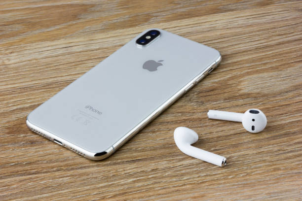 the iphone 10 lies on a wooden table next to the wireless headphones airpods from the apple. - apple computers foto e immagini stock