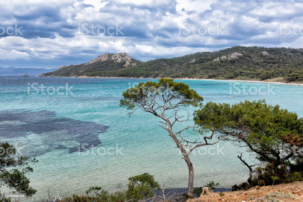 The island of Porquerolles in the Var, in Provence, on the Côte d'Azur The island of Porquerolles is the largest and most western of the three islands of Hyères with its 12.54 km² of surface. It is located 2.6 km southeast of the Fondue Tower, the southern end of the Giens peninsula, and 9.6 km west of the island of Port-Cros.  This is the beach of Notre Dame. Hidden behind a wood, sheltered from the wind, this beautiful white sand beach located north of the island of Porquerolles is fascinatingly beautiful. Less crowded than the other beaches of the island, Notre-Dame beach extends for nearly 800 meters. Then you will be quiet to rest, contemplate the landscape and swim in the turquoise blue sea. This amazing island is the largest and most western of the three islands of Hyères. According to European Best Destinations, an organization that promotes culture and tourism in the Old Continent, this is where the most beautiful beach in Europe is. Beach Stock Photo