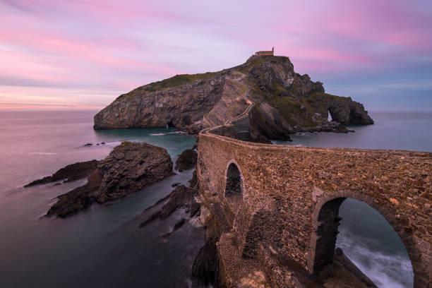 Die kleine Stadt San Juan de Gaztelugatxe und ihre mittelalterliche Brücke mit Treppen bei unglaublichem rosa Sonnenuntergang, Baskenland, Bermeo, Spanien – Foto