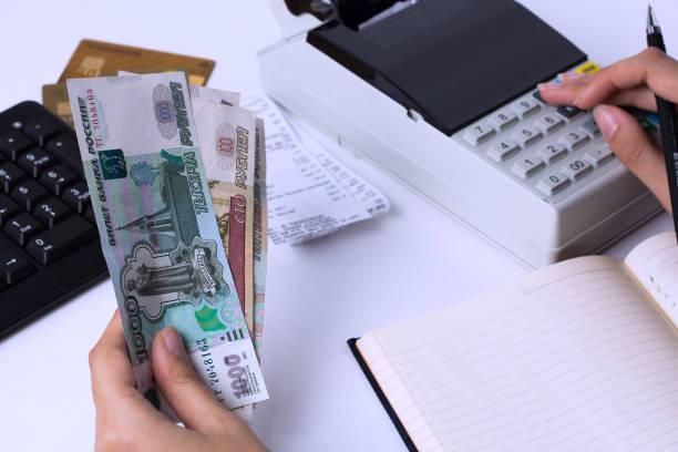 러시아의 임금 문제. 회계사 출납원은 루블로 돈을 계산하고 보고서와 명세서를 채웁니다. 직장에서 사무실 노동자. - 러시아 루블 뉴스 사진 이미지