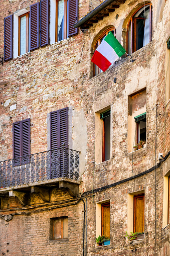 The Italian flag flies from a window in an alley in the historic and medieval heart of Siena in Tuscany, central Italy. Siena is one of the most beautiful Italian cities of art, in the heart of the Tuscan hills, famous for its immense artistic and historical heritage and for the Palio, where the seventeen old districts of the city compete every year in Piazza del Campo in one of the oldest horse racing in the world. Since 1995 the historic center of Siena has been declared a World Heritage Site by UNESCO. Image in high definition format.