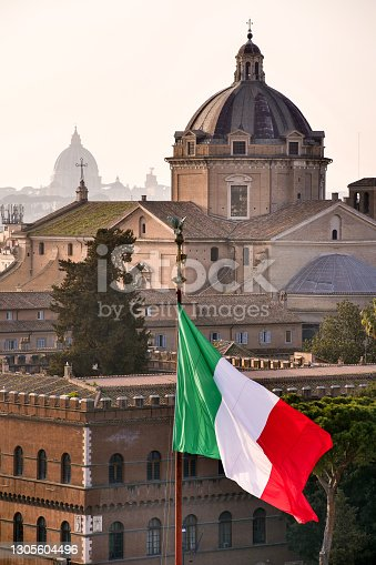 The Italian tricolor flag flies over the Altare della Patria National Monument in the historic center of Rome near the Capitoline Hill (Campidoglio) and Piazza Venezia. Behind the dome of the baroque Chiesa del Gesù and in the background the silhouette of the dome of St. Peter's Basilica. Image in High Definition format.