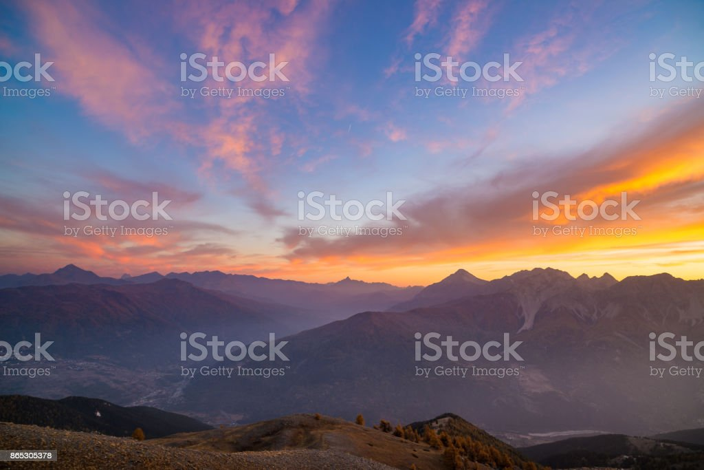 The Italian French Alps at sunset. Colorful sky over the majestic mountain peaks, dry barren terrain and green valleys. Sunburst and backlight expansive view from above. stock photo