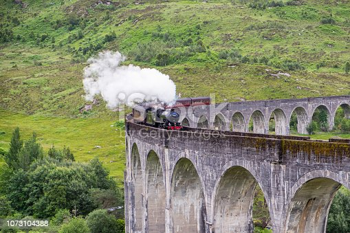 A splendid old locomotive steams across the length of Glenfinnan Viaduct, deep in the Highlands of Scotland.