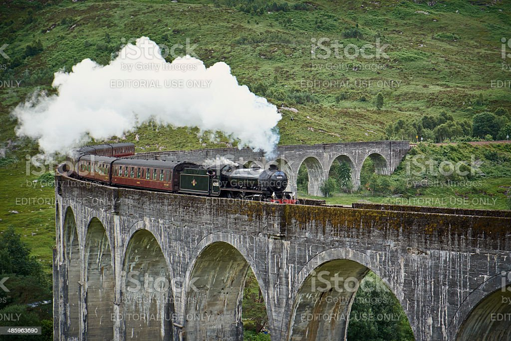 "The Jacobite Locomotive And Glenfinnan Viaduct Glenfinnan, Scotland - July 30, 2015: The splendid old locomotive ""The Lord Of The Isles""/The Jacobite steams across the length of Glenfinnan Viaduct, deep in the Highlands of Scotland.  2015 Stock Photo"