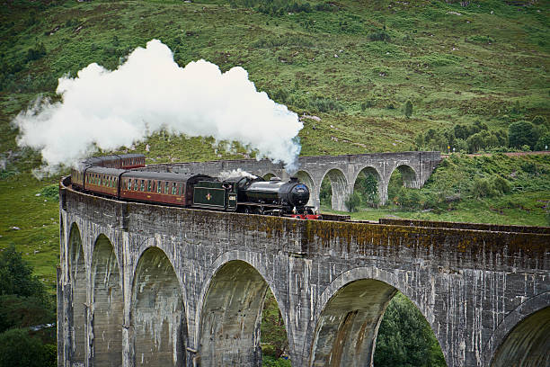 """The Jacobite Locomotive And Glenfinnan Viaduct Glenfinnan, Scotland - July 30, 2015: The splendid old locomotive """"The Lord Of The Isles""""/The Jacobite steams across the length of Glenfinnan Viaduct, deep in the Highlands of Scotland.  railway bridge stock pictures, royalty-free photos & images"""