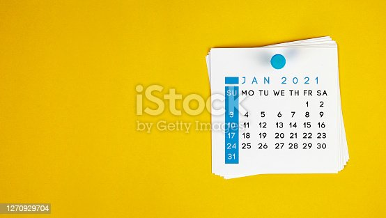 The January 2021 calendar is pinned on a yellow background. Horizontal composition with copy space.