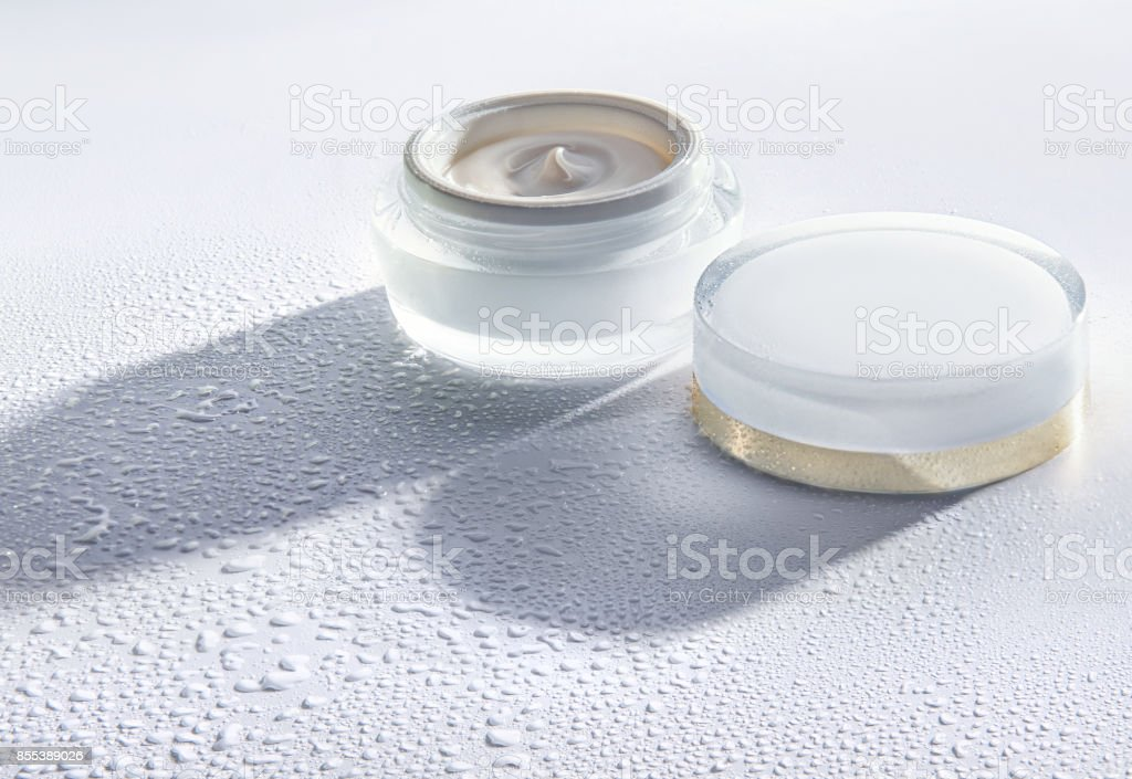 The jar of cosmetic moisturizing cream on the white background with water drops around the jar stock photo