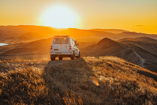 The jeep is standing on the top of the mountain in the sunset. A delightful landscape and the concept of travel, freedom and adventure