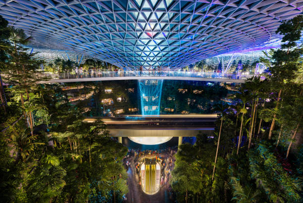 The Jewel at Changi Airport, with the rain vortex indoor waterfall illuminated during the light show, Singapore stock photo