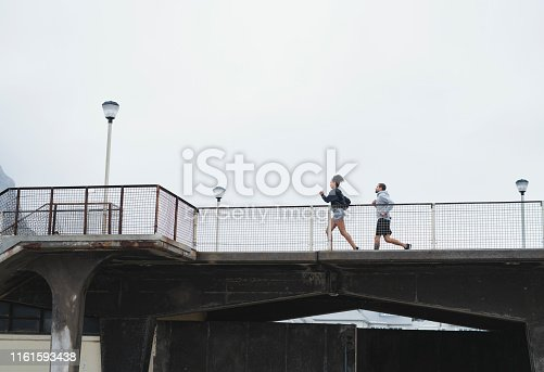 Full length shot of a sporty young couple running on bridge together outdoors