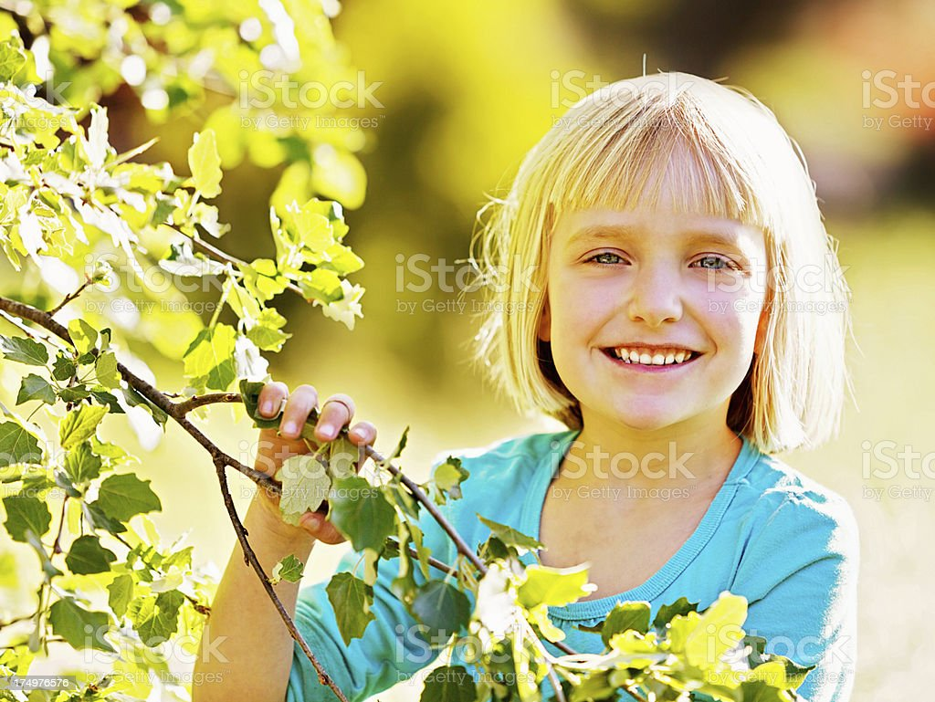 The joys of spring: Cute little blonde girl smiling outdoors stock photo