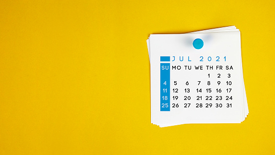 The July 2021 calendar is pinned on a yellow background. Horizontal composition with copy space.
