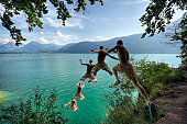 Photo sequence of a young man leaping off a cliff into a blue Alpine lake below on a hot summer day. Slight motion blur on young man as he flies through the air.