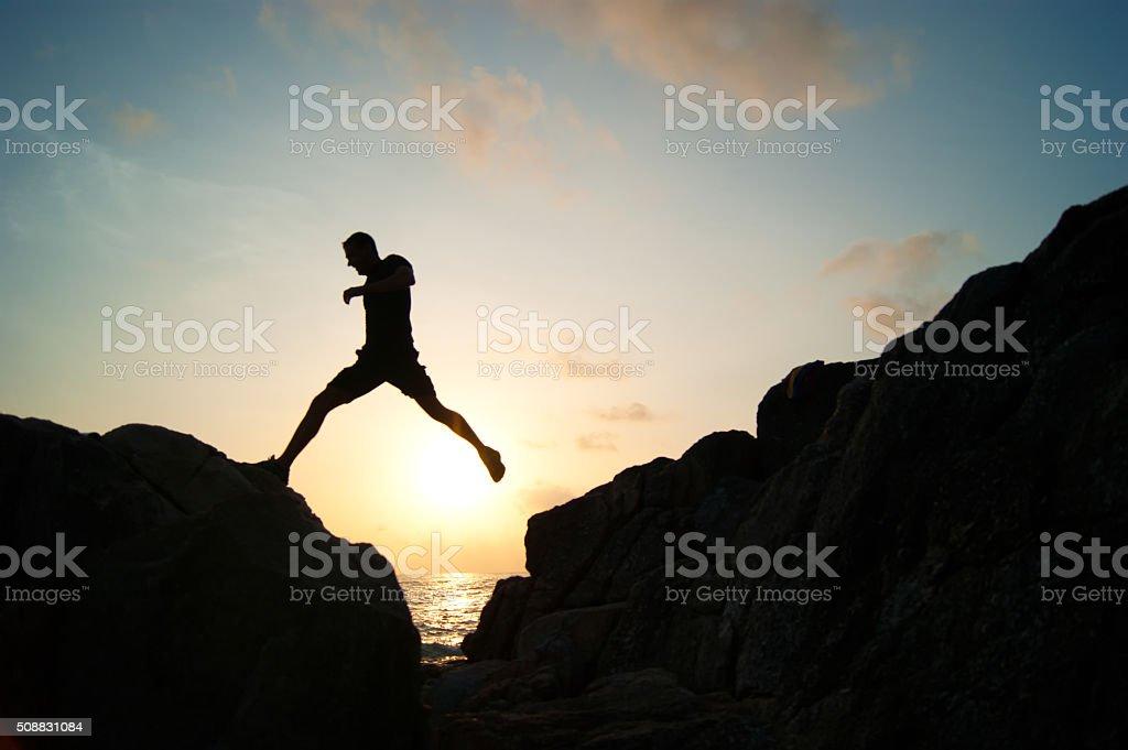 The jumping man on rocks stock photo