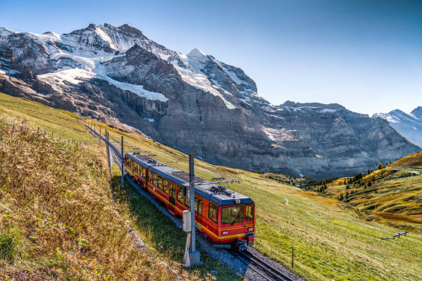 the Jungfrau railway The red train running on the Jungfrau railway with a background view of Jungfrau swiss alps stock pictures, royalty-free photos & images