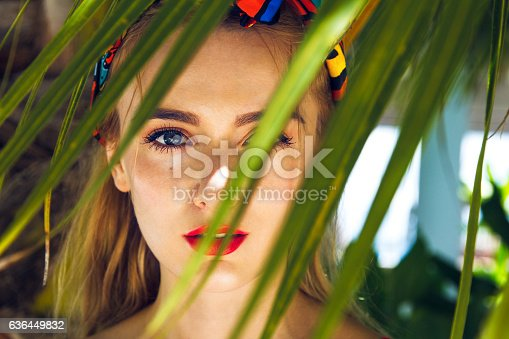 Close up of beautiful blonde model in the jungle scenes, the distinctive red lips and nice colored headband, which fits well with shadows falling on her face and creates a pleasant living atmosphere.