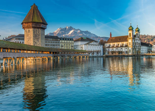 the kapellbrücke (chapel bridge), a covered wooden footbridge spanning diagonally across the reuss in the city of lucerne in central switzerland. - lucerne stock pictures, royalty-free photos & images