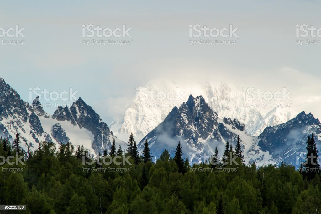 The Kennicott glacier rising high above the trees and the Alaskan mountian stock photo