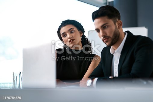 Cropped shot of two young businesspeople sitting together and having a discussion while using a laptop in the office