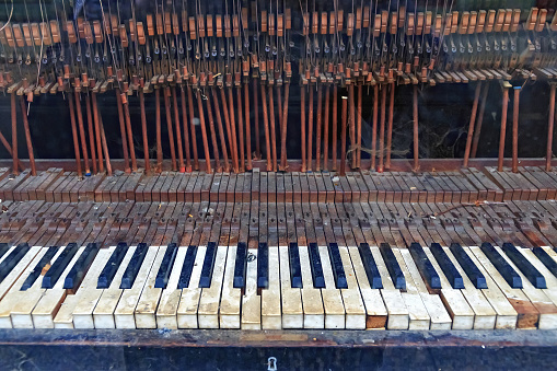 The keyboard of an old vintage piano in ruined condition.