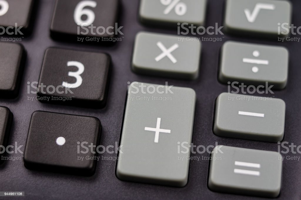 The keyboard of the calculator on a larger scale. Buttons with mathematical markings and numbers. Dark background. stock photo