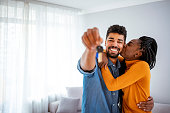 Young smiling African-American couple showing keys to new home hugging looking at camera.