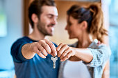 Shot of a cheerful young couple holding a key together to their new home while standing inside during the day