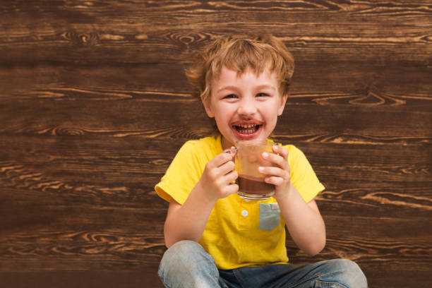 the kid drinking cocoa at home. the kid drinking cocoa at home. hot chocolate stock pictures, royalty-free photos & images