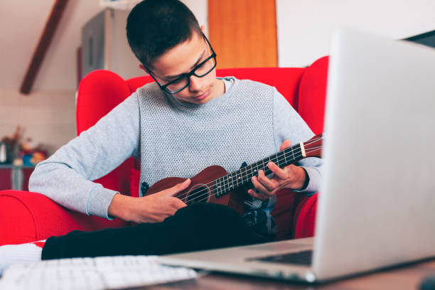 the kid in the red armchair learns to play ukuleles during isolation due to the coronavirus - lepro stock pictures, royalty-free photos & images