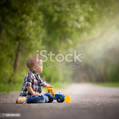 The kid plays with a bright colored tractor on the track in the park. Early development. Child playing outdoors. Lifestyle.